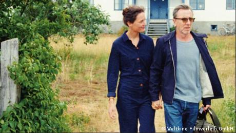 Filmstill von 'Bergman Island': ein Paar hält Händchen, der Mann trägt eine Reisetasche