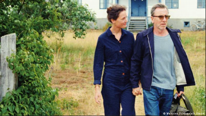 Film still 'Bergman Island': A couple holding hands, with the man carrying luggage.