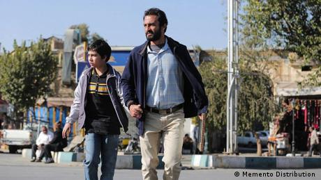 Filmstill von 'A Hero': Mann läuft mit Jungem an der Hand über eine Straße in einer belebten Stadt