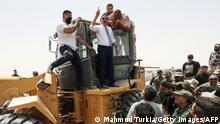 20/06/2021*** Libyan Interim Prime Minister Abdulhamid Dbeibah, waves as he stands atop an excavator on June 20, 2021, in the town of Buwairat al-Hassoun, during a ceremony to mark the reopening of 300-kilometre road between the cities of Misrata and Sirte. - Libya's unity government today reopened the coastal highway linking the country's east and west, that was cut off in 2019 as eastern-based military strongman Khalifa Haftar launched an offensive to seize the capital Tripoli. It connects the war-torn North African country's border with Tunisia to its frontier with Egypt. (Photo by Mahmud TURKIA / AFP) (Photo by MAHMUD TURKIA/AFP via Getty Images)
