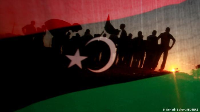 Menschensilhouetten hinter der libyschen Flagge