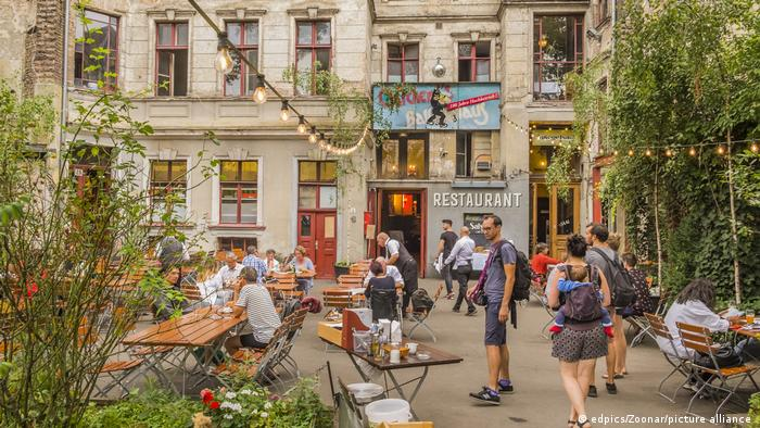 People sitting at outdoor tables at Clärchens Ballhaus restaurant in Berlin, Germany