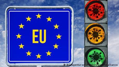 EU sign next to traffic light imprinted with coronaviruses