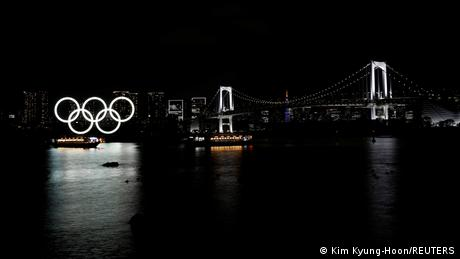 Giant neon Olympic rings next to the Rainbow bridge on the waterfront area of Odaiba Marine Park in Tokyo, Japan