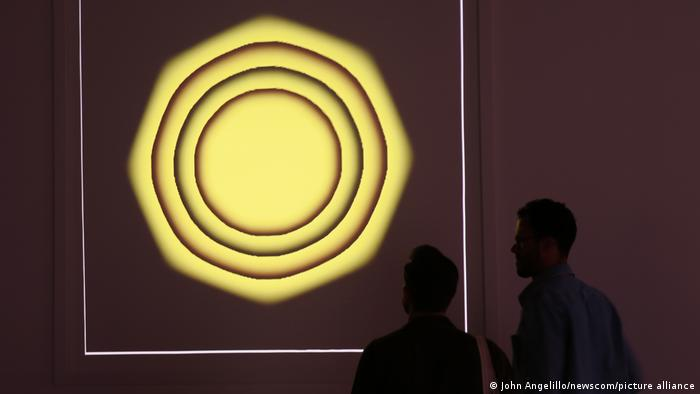 Zwei Männer schauen auf das NFT-Kunstwerk Quantum von Kevin McCoy