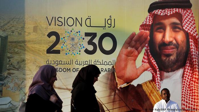 People walk past a banner showing Saudi Crown Prince Mohammed bin Salman, outside a mall in Jeddah.