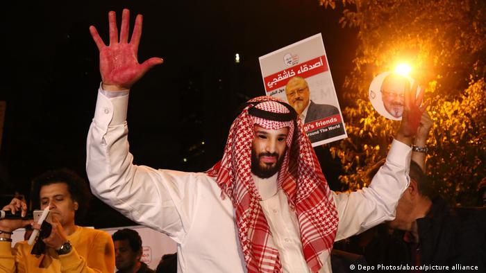 An activist, wearing a mask depicting Saudi Crown Prince Mohammed bin Salman, holds up his hands, painted with fake blood.