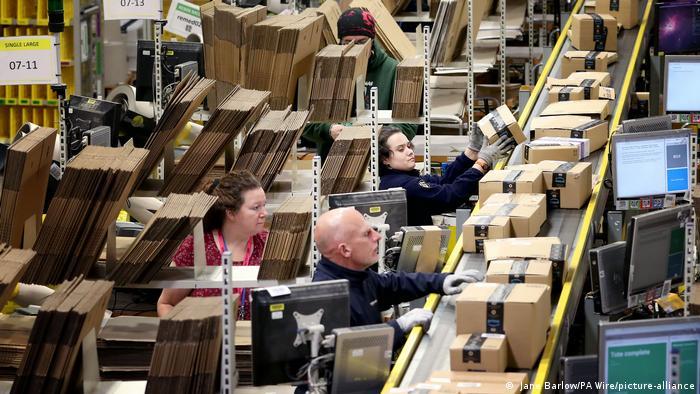 Personal de Amazon etiqueta y empaqueta artículos en la sala de expedición de uno de los mayores almacenes de Amazon en Dunfermline, Escocia.