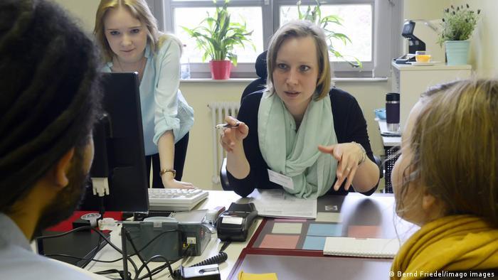 Zwei Sachbearbeiter im Bürgeramt Berlin-Kreuzberg im Gespräch mit zwei Besuchern