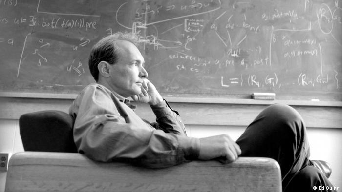 Tim Berners-Lee sitzt vor einer Tafel mit Formeln