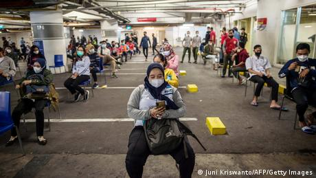 Shoppers wait for Covid-19 coronavirus swab tests before they are allowed to enter a shopping mall in Surabaya, Indonesia