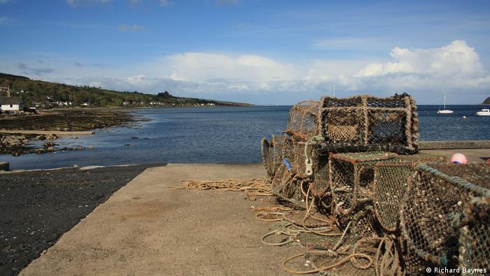 Creel fishing traps sitting on a stone pier in Lamlash Bay