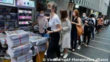 People queue up for last issue of Apple Daily at a newspaper booth at a downtown street in Hong Kong, Thursday, June 24, 2021. Across Hong Kong, people lined up early Thursday to buy the last print edition of the last remaining pro-democracy newspaper. ( AP Photo/Vincent Yu)