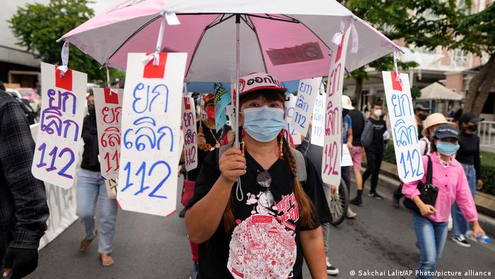 A Thai protester wears a face mask with the umbrella with sign saying No to Article 112