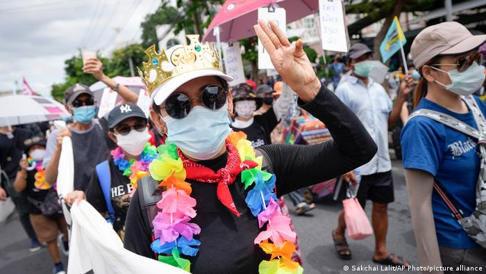 A woman wearing a colorful garland, a golden toy crown, sunglasses and a medicial mask holds up her hand in a three-finger salute. Behind her other people are wearing masks and marching along in a protest.