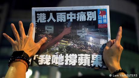 A person holds up a copy of Apple Daily's last edition