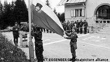 APA4121187-2 - 19052011 - SEEBERG - SLOWENIEN: ZU APA-TEXT AI - Männer der slowenischen Miliz hissen am 29. Juni 1991 nach der Rückeroberung der österreichischen-slowenischen Grenzstation am Seebergsattel, Bezirk Völkermarkt, die Fahne. Die Unabhängigkeit Sloweniens von Jugoslawien musste in einem Zehn-Tage-Krieg mit der Volksarmee erkämpft werden. APA-FOTO: GERT EGGENBERGER - 19910627_PD0020