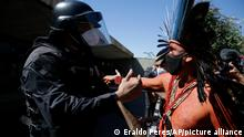 An Indigenous leader argues with a police officer guarding Congress in Brasilia, Brazil, Tuesday, June 22, 2021. Indigenous, who are camping in the capital to oppose a proposed bill they say would limit recognition of reservation lands, clashed with police preventing the protesters from entering Congress. (AP Photo/Eraldo Peres)