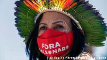 A woman wears a mask stamped with a message that reads in Portuguese; Out Bolsonaro in reference to President Jair Bolsonaro, during a protest opposing a proposed bill that Indigenous protesters say would limit recognition of reservation land, outside Congress in Brasilia, Brazil, Tuesday, June 22, 2021. (AP Photo/Eraldo Peres)
