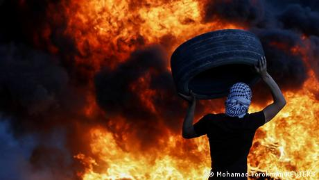 A Palestinian demonstrator carries a tire amid preparations for a night protest against Israeli settlements in Beita in the Israeli-occupied West Bank