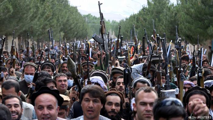 Blick auf die Köpfe einer sehr großen Gruppe von Männern, die Gewehre in die Luft halten. Sie stehen auf einer Straße, die auf beiden Seiten von Nadelbäumen gesäumt ist