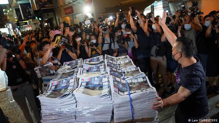 Große Palette mit Zeitungen, umringt von Fotografen