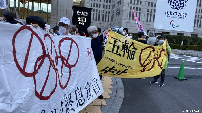 protesters hold banners with ant-Olympics slogans on them in English and Japanese