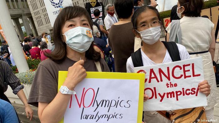 Protesters in Tokyo holding placards against Olympics