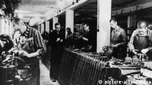 Das undatierte Archivbild zeigt Häftlinge des Konzentrationslagers Dachau bei der Herstellung von Waffen. Eineinhalb Jahre nach Aufnahme der schwierigen deutsch-amerikanischen Verhandlungen hat der Bundestag die Entschädigung ehemaliger NS-Zwangsarbeiter endgültig geregelt. In namentlicher Abstimmung billigte eine breite Mehrheit der Abgeordneten am Donnerstag (06.07.2000) das Gesetz für die Zwangsarbeiter-Stiftung. Nachdrücklich und begleitet von heftiger Kritik wurden die zehntausenden säumigen deutschen Unternehmen aufgefordert, endlich ihren Beitrag für die Stiftung zu leisten und die Verantwortung für ihre Geschichte in der Nazi-Zeit zu übernehmen. Mit der Annahme des Stiftungsgesetzes werden 55 Jahre nach Ende des Zweiten Weltkrieges voraussichtlich schon in diesem Jahr die ersten der noch lebenden 1,2 Millionen Opfer des Nazi-Terrors entschädigt. dpa (nur s/w; zu dpa 2655 am 06.07.2000)