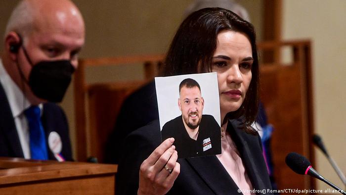 Светлана Тихановская держит фото своего мужа, который находится в тюрьме