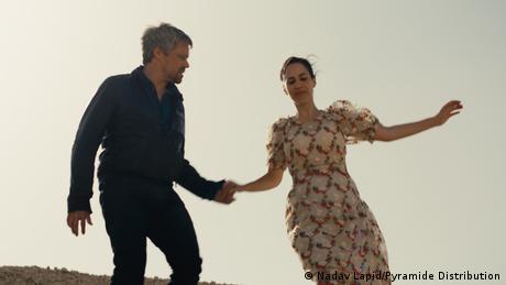 Filmstill von 'Ahed's Knee': Ein Mann und eine Frau halten sich an der Hand.