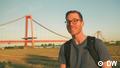 Junger Mann lächelt vor einer roten Hängebrücke in die Kamera