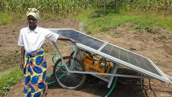 Mobile solar water pump in Rwanda, farmer stands in front