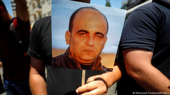 Man holding placard with picture of Nizar Banat