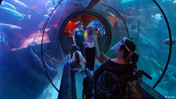 Blick in einen Tunnel, der durch ein Aquarium führt. Vorne rechts sitzt eine Frau im Rollstuhl mit Gesichtsvisier, die hochschaut. Im Hintergrund sind drei junge Frauen mit Mund-Nasen-Schutz zu erkennen