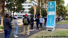 People wait in line outside a coronavirus disease (COVID-19) vaccination centre at Sydney Olympic Park in Sydney, Australia, June 23, 2021. REUTERS/Jane Wardell
