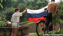 05/07/1991*** Two Slovenian youths hold up the flag of their breakaway republic as a Yugoslavian army T-55tank is transported past them on its way back to military depot 05 July 1991 in Ljubliana. The withdrawal of federal troops and artillery in compliance with the new cease-fire agreement is being seen by some Slovenians as astep forward in securing independence. AFP PHOTO MIKE PERSSON (Photo by MIKE PERSSON / AFP)