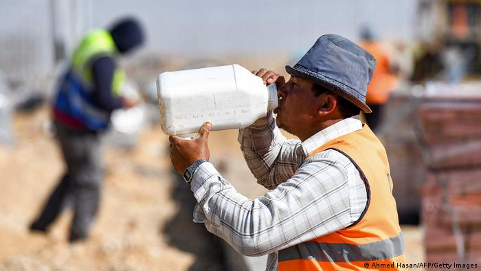 A construction site worker drinks from a large white canister on a building site