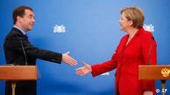 Russian President Dmitry Medvedev, left, and German Chancellor Angela Merkel shake hands during a press conference
