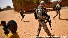 GAO, MALI - MARCH 07: Children follow soldiers of the Bundeswehr, the German Armed Forces, after leaving a weekly cattle market on the outskirts of Gao on March 7, 2017 in Gao, Mali. The soldiers of the Bundeswehr try to gather information on prices of meat and movement around the city, as well as possible suspects among farmers, as each week locals and Touareg nomads gather at the market to trade their cattle including Camels, Cows, Sheep and clothing. U.N.-led MINUSMA (United Nations Multidimensional Integrated Stabilization Mission) troops are assisting the Malian government in its struggle against rebels that include a Tuareg movement (MNLA) and several Islamic armed groups, among them Al-Qaeda, in the north of Mali. Rebels have conducted a series of terror attacks to destabilize the current government in recent years. The Bundeswehr has committed helicopters and 750 soldiers to the MINUSMA mission as well as 147 soldiers to the EUTM mission (European Trainings Mission Mali) to train government troops. In mid-April the Bundeswehr is to deploy four «Tiger«combat helicopter. (Photo by Alexander Koerner/Getty Images)
