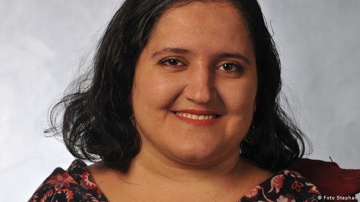 Porträt einer jungen Frau mit schulterlangen dunklen Haaren, die in die Kamera lächelt
