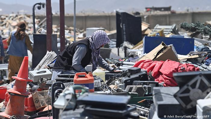People look for usable items at a junkyard near the Bagram Air Base