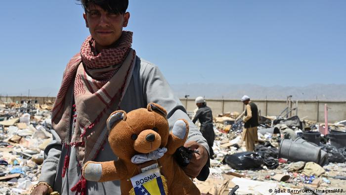 A man with a stuffed teddy bear at the Bagram junkyard