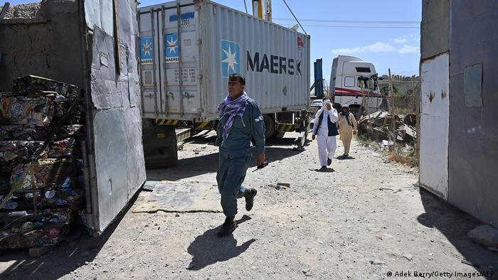Workers unload a container at a junkyard near the Bagram Air Base in Bagram