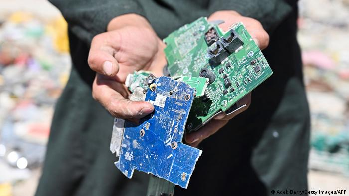 A man holding electronic waste he found at the dump