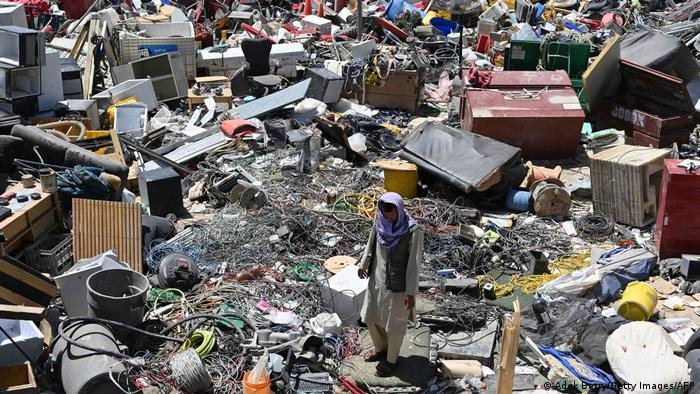 A man surrounded by garbage in Bagram