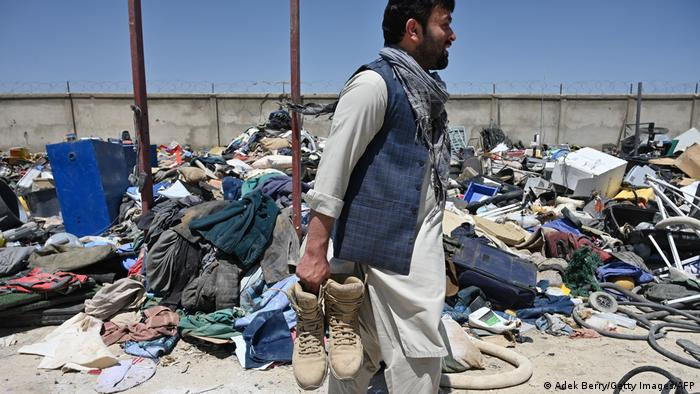 A man holds shoes as he selects valuable items at a recycling workshop near the Bagram Air Base