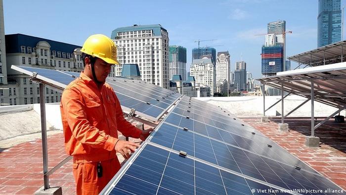 A worker installs solar panels in Vietnam
