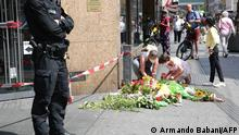A policeman stands guard as people place flowers and candles at a makeshift memorial in tribute to the victims of a deadly attack in the city center of Wuerzburg, southern Germany, on June 26, 2021. - Investigators were racing to pinpoint the motive of a man who went on a knife rampage in the German city of Wuerzburg, killing three people and leaving five seriously injured. The suspect, a 24-year-old Somali who arrived in Wuerzburg in 2015, staged the attack in the city centre on the evening of Friday, June 25, 2021, striking at a household goods store before advancing to a bank. (Photo by ARMANDO BABANI / AFP)