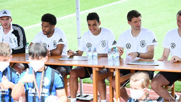 Jamal Musiala (center) signs autographs with his Germany teammates during Euro 2020.